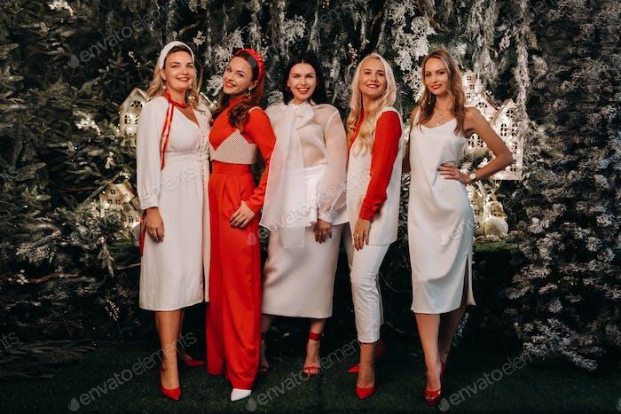 sexy Frauen in festlichen weißen und roten Kleidern stehen auf einem weihnachtlichen Hintergrund