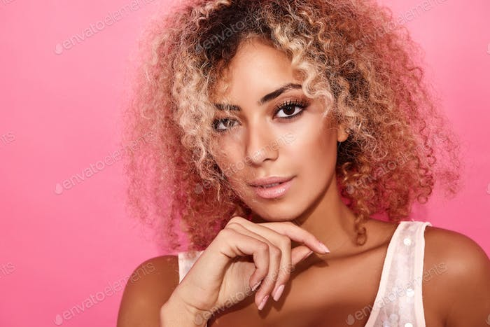 Beautiful woman with afro curls hairstyle posing in studio