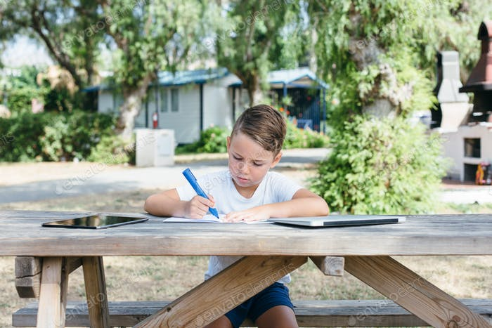 Schoolchild with studies at table outside