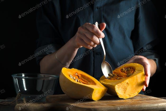 Löffel in der Hand, Kürbishälften auf einem Tisch auf einem blauen Hintergrund