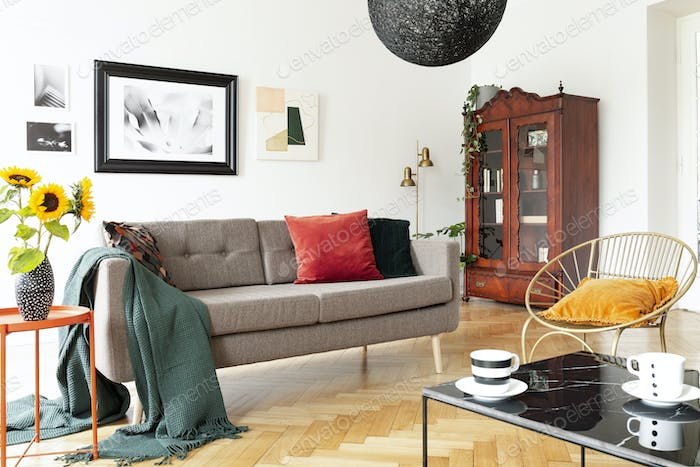 Armchair next to couch with blanket in white apartment interior