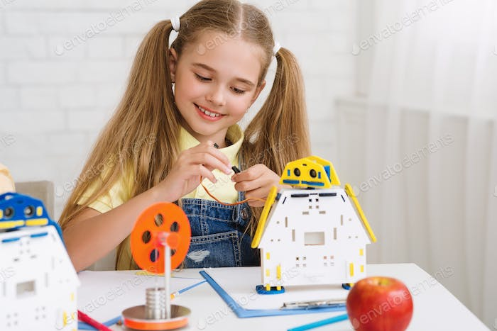 Stem education. School girl constructing robot at lesson