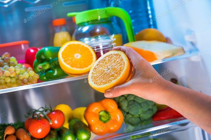 Frau nimmt die Orange aus dem offenen Kühlschrank.