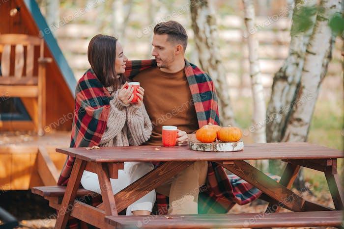 Молодая пара с кофе на дворе своего дома осенью