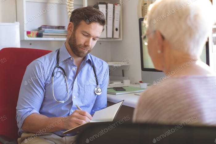 Front view of Caucasian male doctor and senior woman interacting with each other in clinic