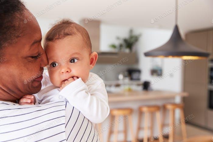 Liebevolle Großmutter halten 3 Monat alt Baby Enkelin in Küche zu Hause