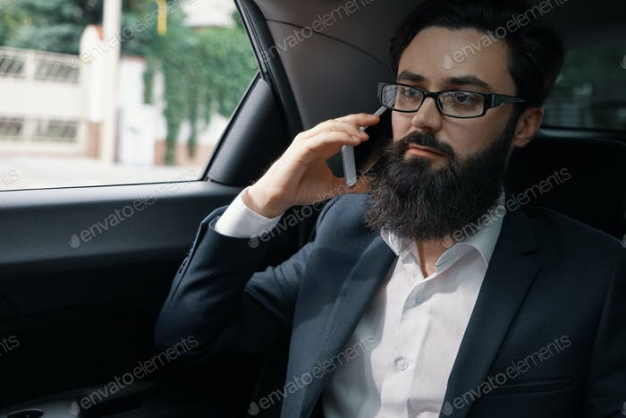 A businessman while traveling by car in the back seat using a sm
