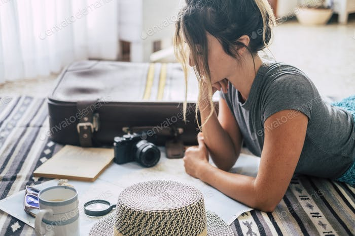 Caucasian woman planning vacation travel with map and guide at home, female people plan