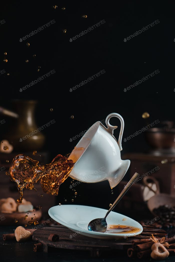 Falling coffee cup with a dynamic splash in a dark scene with cezve, saucer and teaspoon