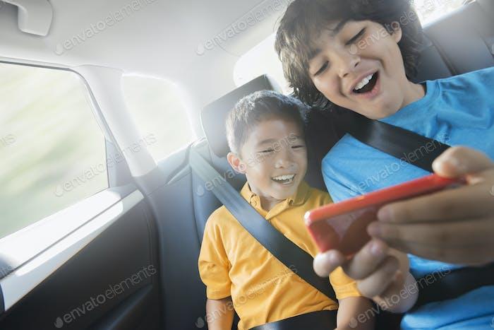 Zwei Kinder, die auf dem Rücksitz eines Autos unterwegs sind, teilen sich ein Handheld-Spieletablett.