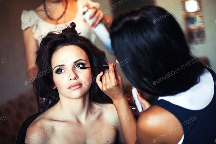 wedding. Young beautiful girl applying make-up by make-up artist