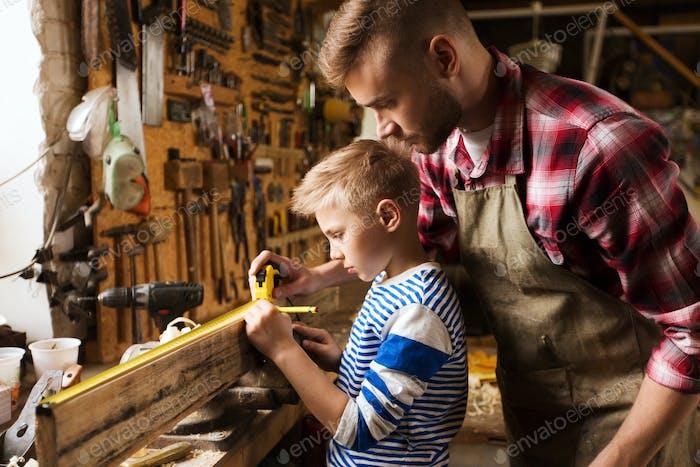 Vater und Sohn mit Lineal messen Holz in der Werkstatt