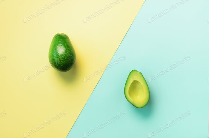 Avocado sliced with seed, whole fruit on blue and yellow background. Top view. Pop art design