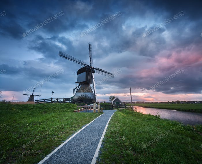 Traditional dutch windmills near water canals with cloudy sky, l