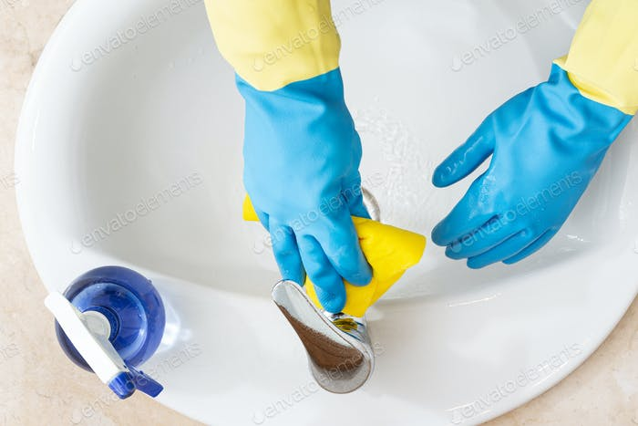 Hands with gloves cleaning a bathroom with a yellow rag
