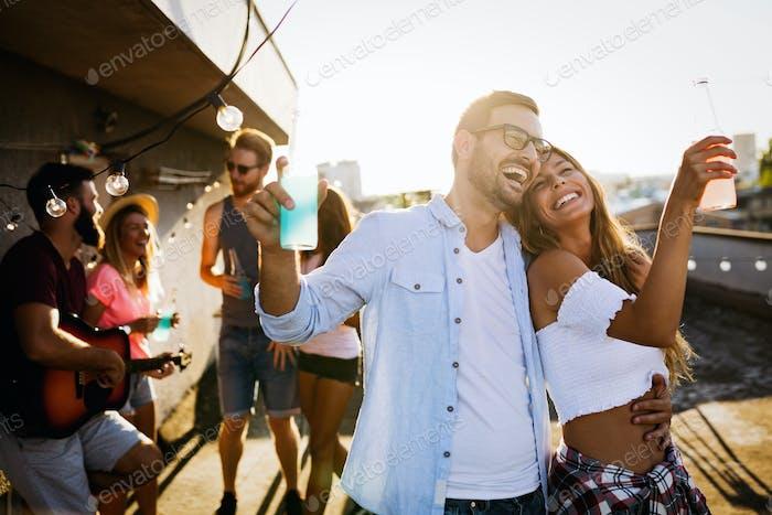 Glückliches junges Paar trinken Cocktail auf dem Dach