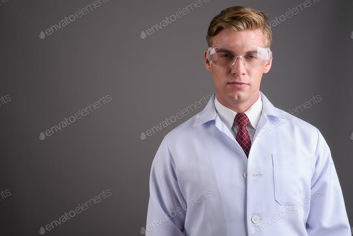 Young handsome man doctor with blond hair against gray backgroun