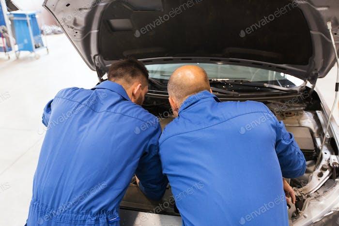 mechanic men repairing car at workshop