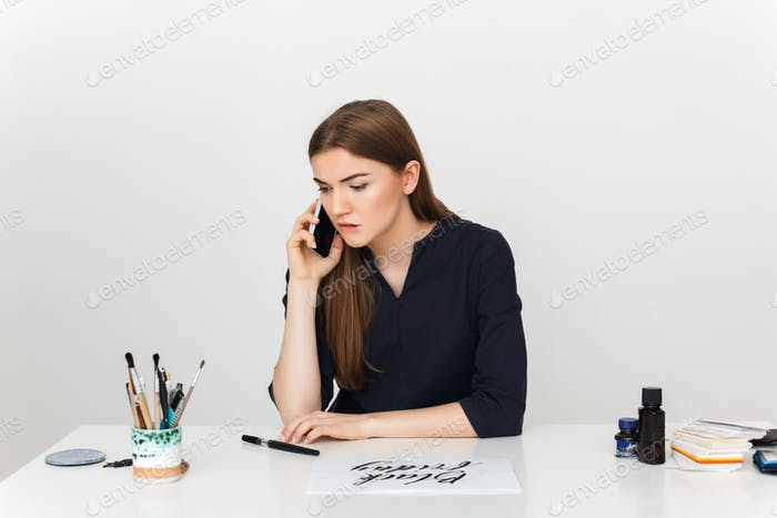 Portrait of young beautiful girl sitting at the white desk and talking on her cellphone