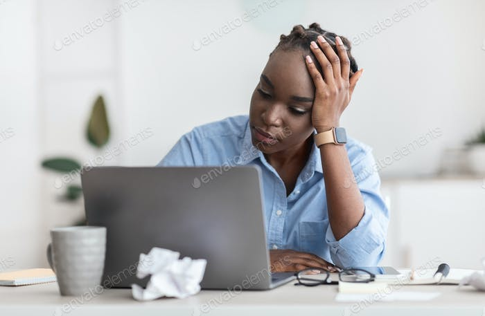 Creativity Crisis. Stressed black female freelancer looking at laptop screen with despair