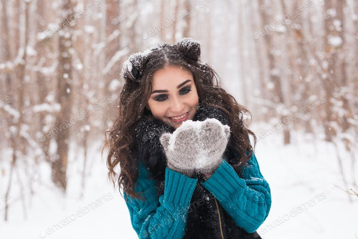 Beauty and people concept - Happy brunette woman in a winter forest is smiling and holding snow in