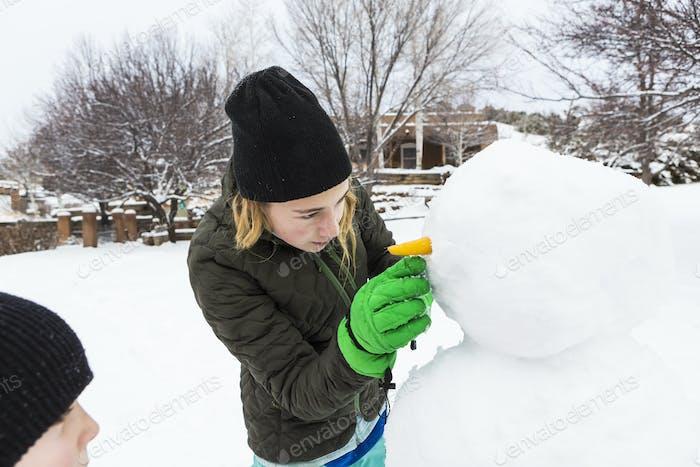 Teenager-Mädchen und ihr jüngerer Bruder bauen einen Schneemann in einem Garten
