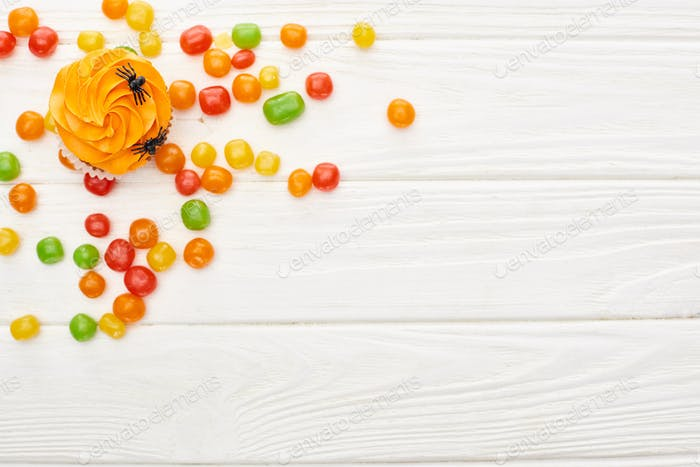 Top View of Colorful Bonbons Near Cupcake With Spiders on White Wooden Table, Halloween Treat