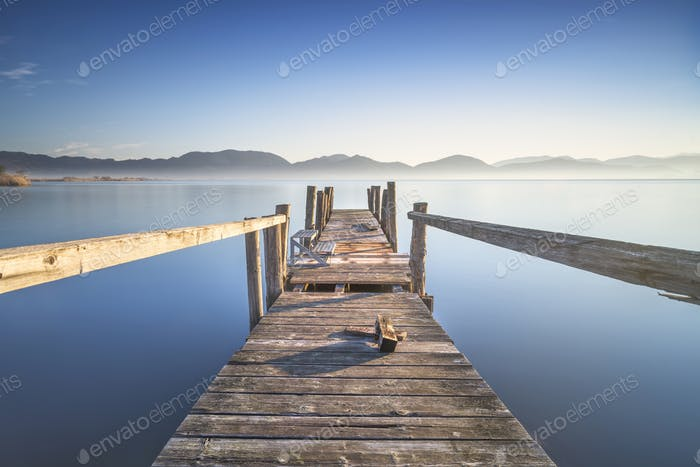 Wooden pier or jetty and lake at sunrise. Torre del lago Puccini Versilia Tuscany, Italy