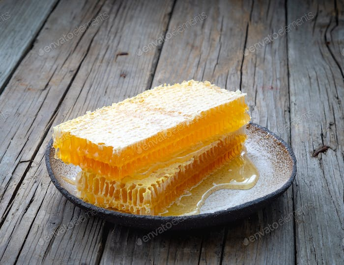 Thumbnail for honey in honeycomb, close-up, on white ceramic plate, on wooden rustic table,