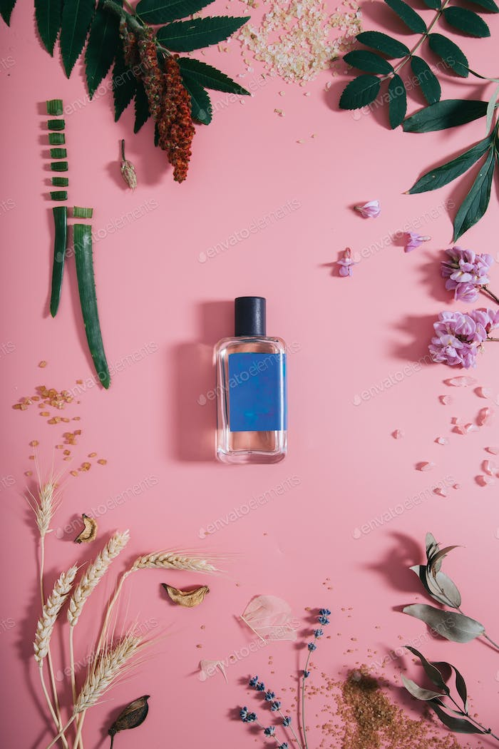 Perfume bottle with blue sticker in flowers on pink background.