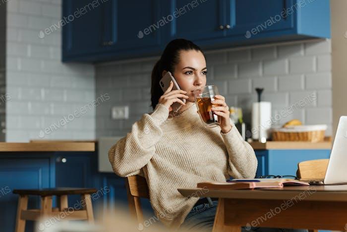 Lächelnde schöne Frau im Gespräch auf dem Handy