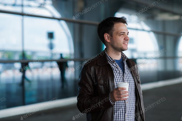 Stylish handsome young male traveller with bristle standing outdoors near the airport terminal. Man
