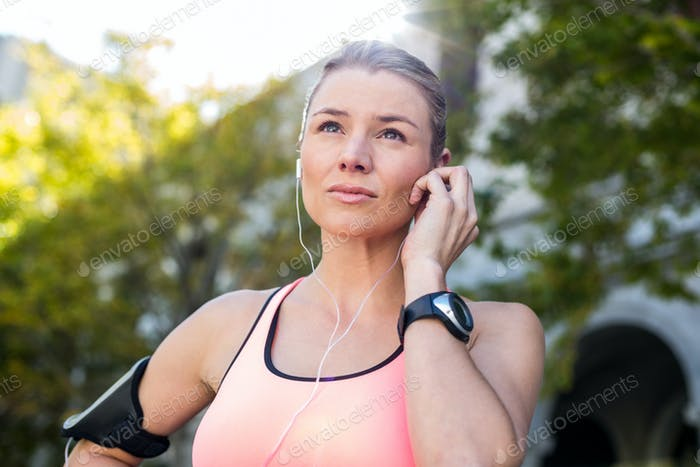 A beautiful athlete putting her headphones on a sunny day