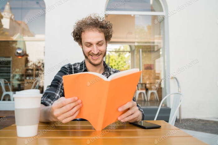 Man enjoying free time and reading a book.