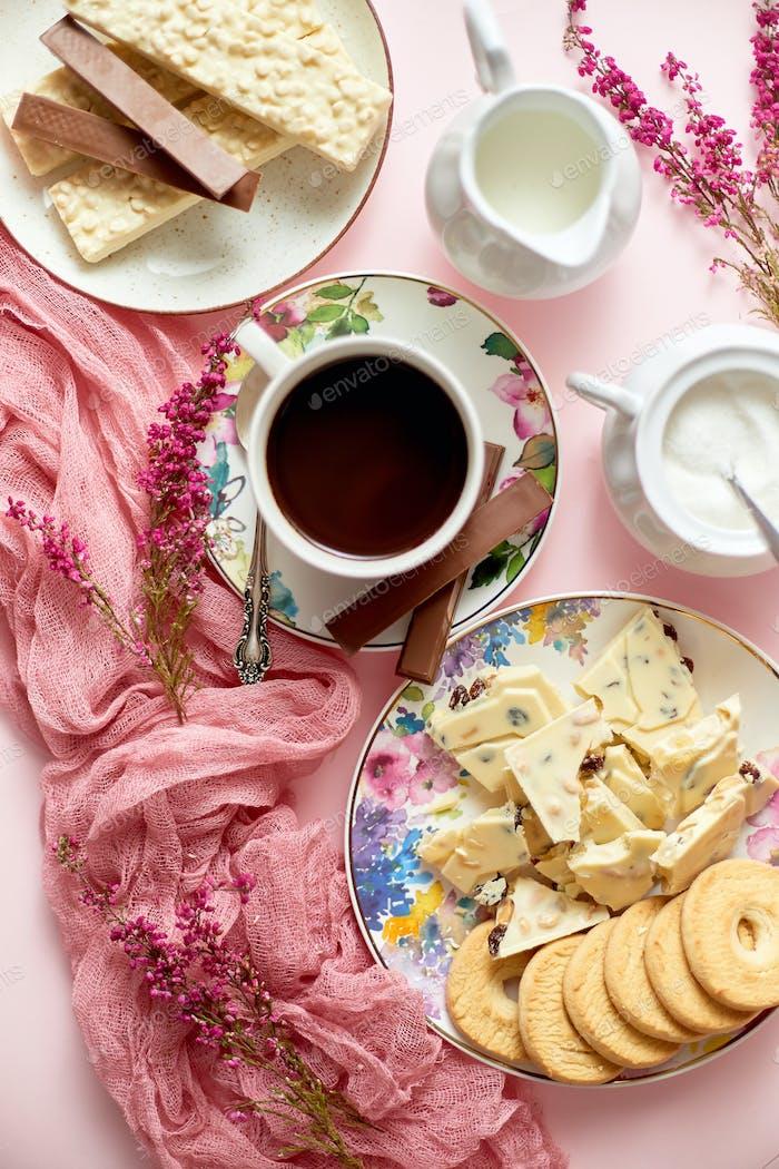 Heiße Schokolade oder Kakao in einer Tasse mit verschiedenen Süßigkeiten an den Seiten. Weißer Schokoriegel und Kekse