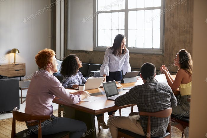 Young woman standing to address colleagues at a work meeting