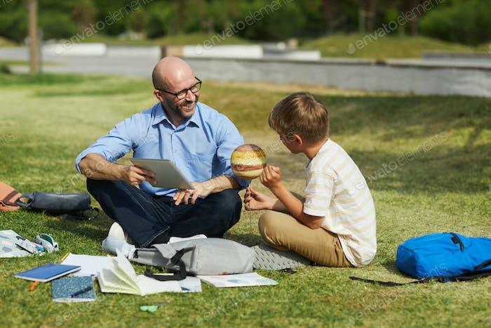 Junge im Gespräch mit dem Lehrer während des Unterrichts im Freien