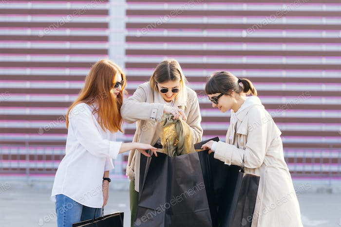 Young women looking for something in your bags
