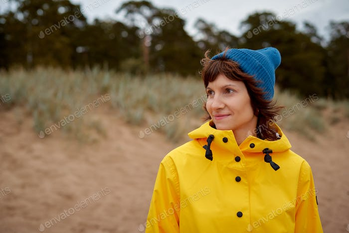 One with nature. Mature beautiful woman looking to forest in bright yellow jacket and blue hat