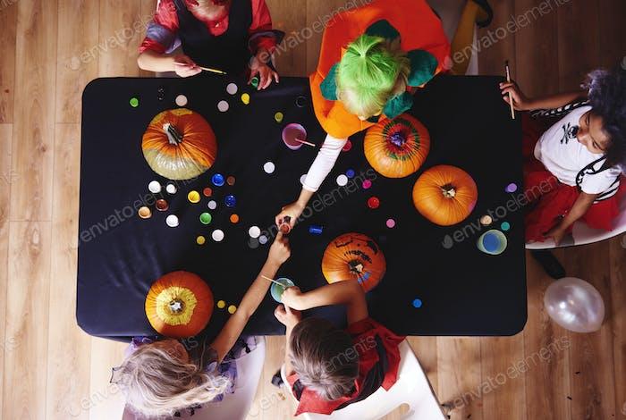 Kids in costume decorating a pumpkin