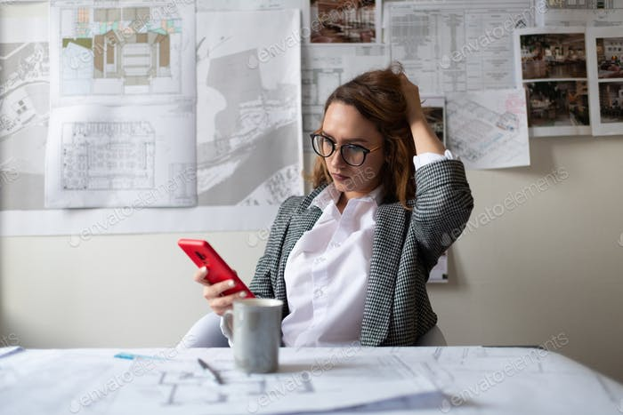 Thoughtful architect browsing smartphone in office