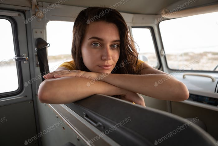 Beautiful woman sitting in camper van and looking at the camera against beach in background