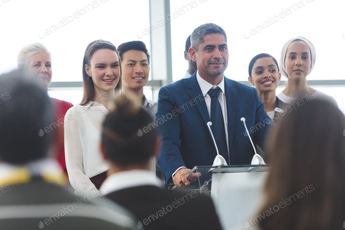 Businessman standing on podium with diverse colleagues and speaking at business seminar in office