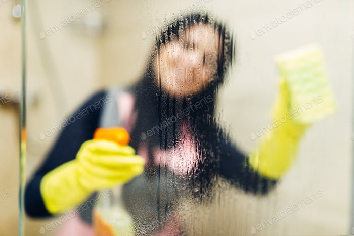 Maid in gloves cleans glass with a cleaning spray
