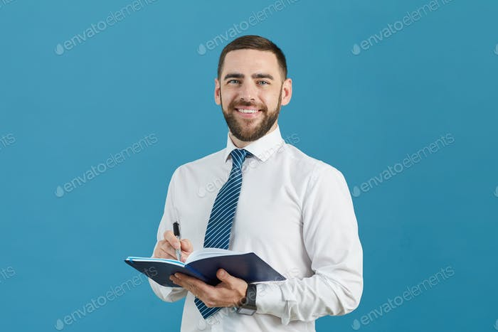 Business assistant making notes in diary
