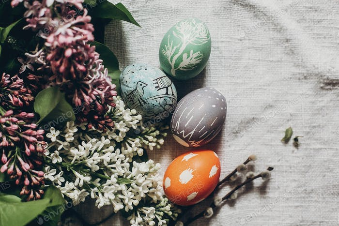 easter eggs with lilac flowers on rustic background