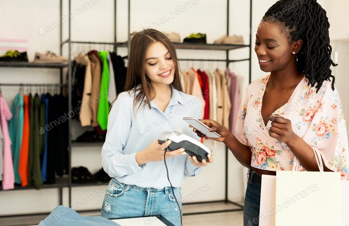 Happy Afro Girl Paying Via Cellphone In Fashion Boutique