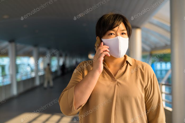 Overweight Asian woman with mask talking on the phone in the city