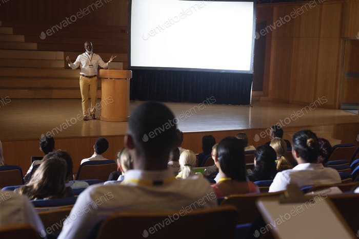 Front view of matured African-American businessman standing and giving presentation in auditorium
