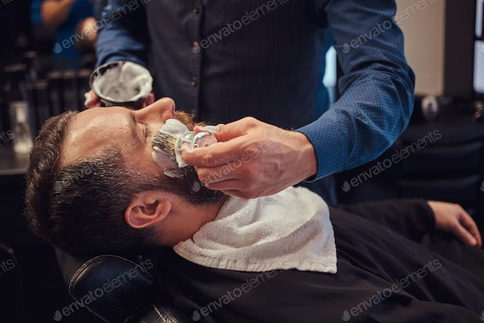 A master hairdresser prepares the face for shaving and smears the face
